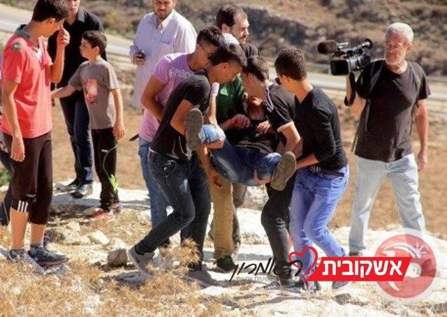 פלסטינים מפנים מפגין ששאף גז מדמיע ברמאללה (צילום ארכיון: מען).